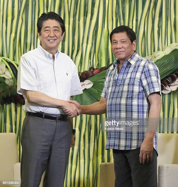 Japanese Prime Minister Shinzo Abe and Philippine President Rodrigo Duterte shake hands before their talks to strengthen personal ties at the...