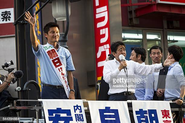 Japanese Prime Minister Shinzo Abe and President of the ruling Liberal Democratic Party and candidate Kentaro Asahi salute the voters during the July...