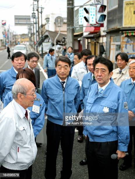 Japanese Prime Minister Shinzo Abe and Restoration Minister Takumi Nemoto receive an explanation from Namie Town Mayor Tamotsu Baba during their...