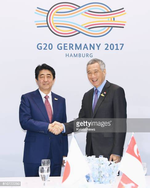 Japanese Prime Minister Shinzo Abe and Singapore Prime Minister Lee Hsien Loong shake hands before their talks in Hamburg Germany on July 8 on the...