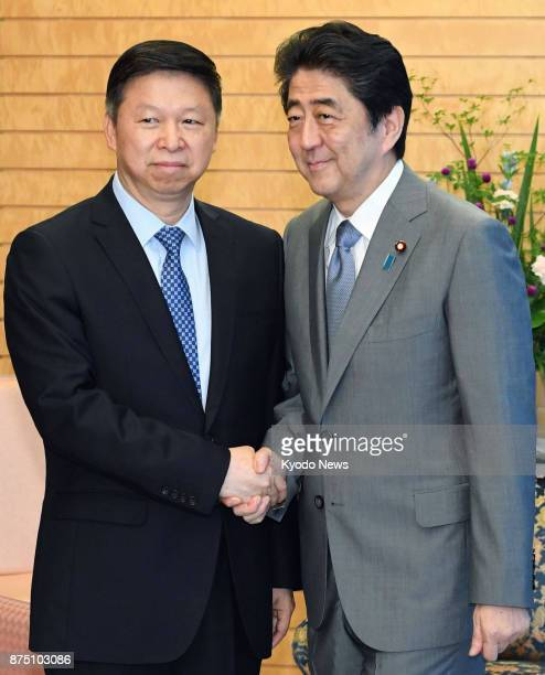 Japanese Prime Minister Shinzo Abe and Song Tao head of the Chinese Communist Party's International Department shake hands in Tokyo on Aug 8 2017...