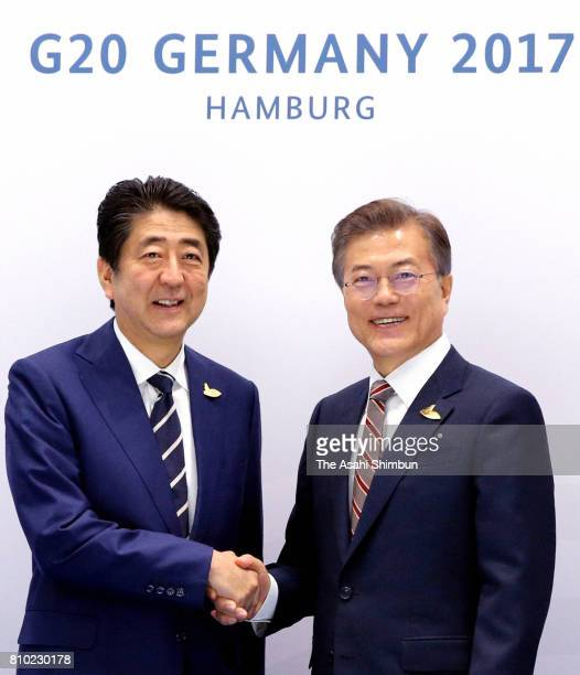 Japanese Prime Minister Shinzo Abe and South Korean President Moon Jaein shake hands prior to their bilateral meeting on the sidelines of the G20...