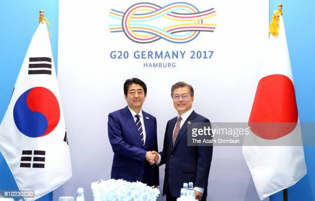 Japanese Prime Minister Shinzo Abe and South Korean President Moon Jae-in shake hands prior to their bilateral meeting on the sidelines of the G20...