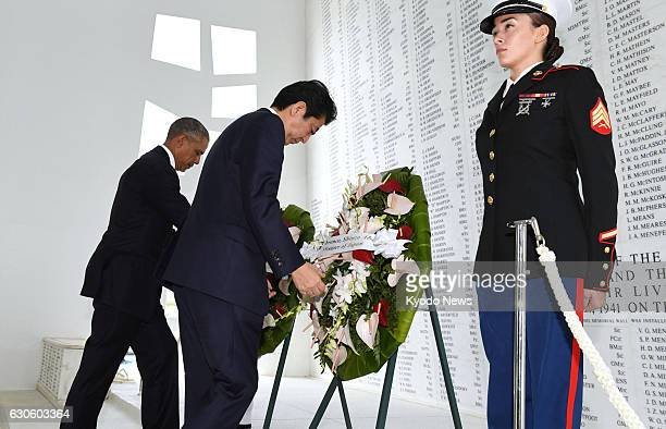 Japanese Prime Minister Shinzo Abe and US President Barack Obama lay wreaths at the USS Arizona Memorial at Pearl Harbor in Hawaii on Dec 27 to...