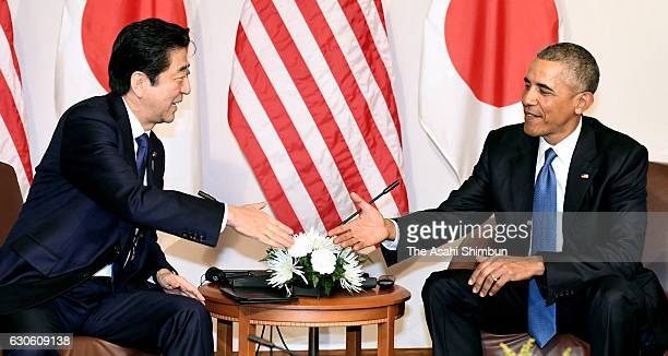 Japanese Prime Minister Shinzo Abe and US President Barack Obama shake hand prior to their meeting on December 27 2016 in Honolulu Hawaii Abe visits...