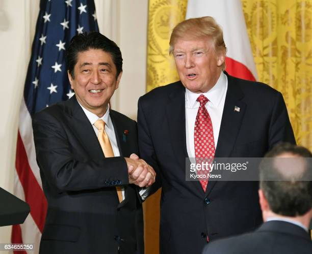 Japanese Prime Minister Shinzo Abe and US President Donald Trump shake hands after a joint press conference at the White House in Washington on Feb...