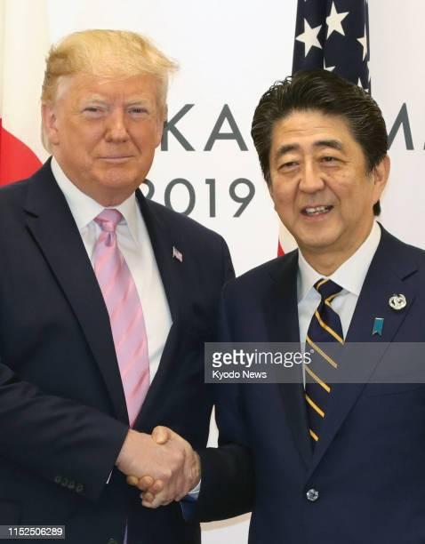 Japanese Prime Minister Shinzo Abe and U.S. President Donald Trump shake hands during their meeting in Osaka on June 28 on the sidelines of the Group...
