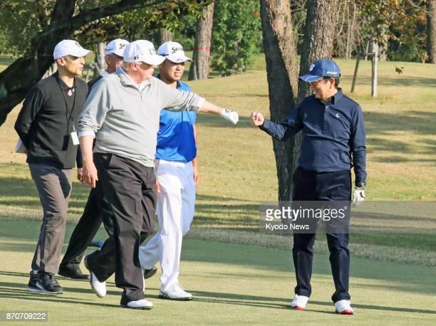 Japanese Prime Minister Shinzo Abe and US President Donald Trump fistbump before professional golfer Hideki Matsuyama at Kasumigaseki Country Club in...