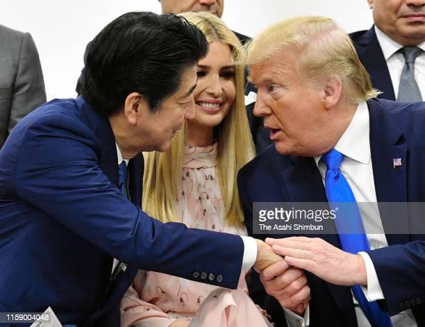 Japanese Prime Minister Shinzo Abe and US President Donald Trump talk while advisor to US President Ivanka Trump listens during the women's...