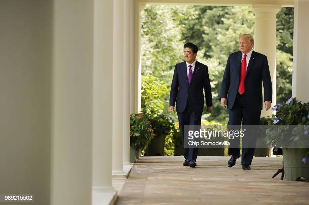 Japanese Prime Minister Shinzo Abe and US President Donald Trump walk along the Rose Garden colonnade as they arrive for a joint news conference at...