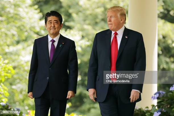Japanese Prime Minister Shinzo Abe and U.S. President Donald Trump walk along the Rose Garden colonnade as they arrive for a joint news conference at...