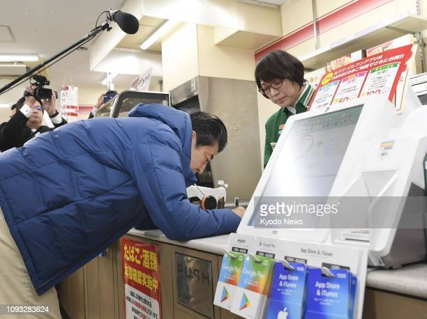 Japanese Prime Minister Shinzo Abe applies for an emoney card at a convenience store in a shopping street in Tokyo's Shinagawa Ward on Feb 2 2019...