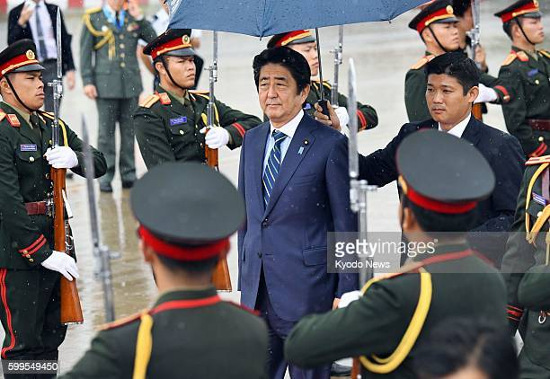 Japanese Prime Minister Shinzo Abe arrives at the airport in Vientiane Laos on Sept 6 to attend a summit of ASEAN nations and the East Asia Summit...