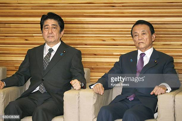 Japanese Prime Minister Shinzo Abe attends a Cabinet meeting in Tokyo on Dec 22 together with Finance Minister Taro Aso The Cabinet approved a...