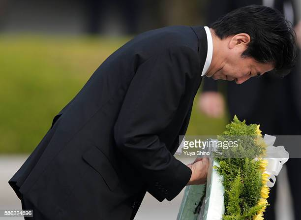 Japanese Prime Minister Shinzo Abe bows as he lays a wreath during the Hiroshima Peace Memorial Ceremony at Hiroshima Peace Memorial Park on August 6...