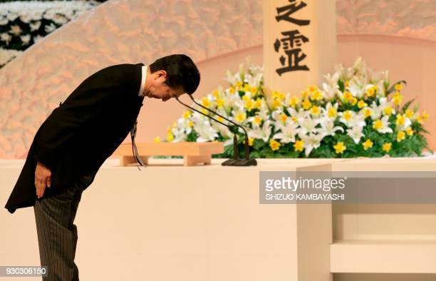 TOPSHOT Japanese Prime Minister Shinzo Abe bows to Prince Akishino and Princess Kiko in front of an altar for victims of the 2011 earthquake and...
