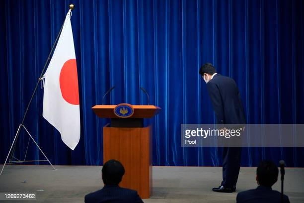 Japanese Prime Minister Shinzo Abe bows to the national flag at the start of during a press conference at the prime minister official residence on...