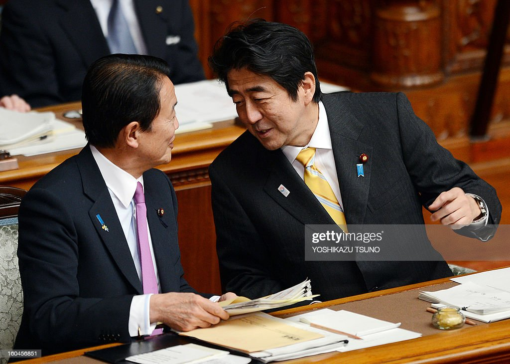 Japanese Prime Minister Shinzo Abe (R) chats with Finance Minister Taro Aso (L) at the Upper House's plenary session at the National Diet in Tokyo on February 1, 2013. Japan's hawkish Prime Minister Shinzo Abe told lawmakers he would release a new statement on the World War II, a move likely to set nerves on edge in China and beyond. AFP PHOTO / Yoshikazu TSUNO