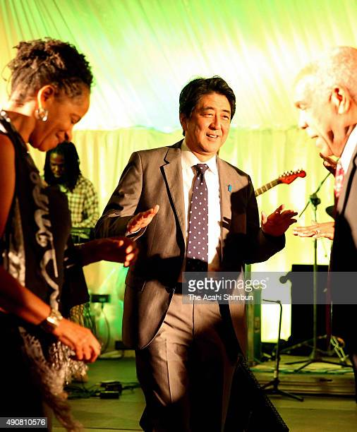 Japanese Prime Minister Shinzo Abe dances during the welcome dinner at SimpsonMiller's official residence on September 30 2015 in Kingston Jamaica...