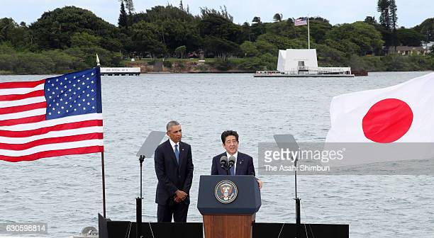 Japanese Prime Minister Shinzo Abe delivers remarks while US President Barack Obama listens at Joint Base Pearl Harbor Hickam's Kilo Pier on December...
