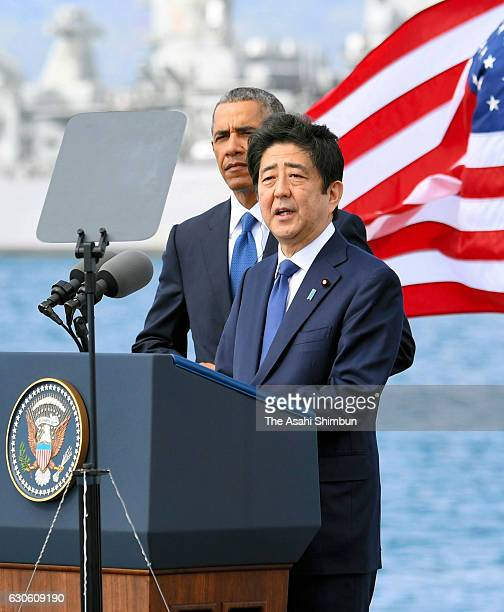Japanese Prime Minister Shinzo Abe delivers remarks while US President Barack Obama listens at Joint Base Pearl Harbor Hickam's Kilo Pier on December...