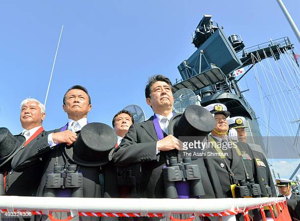 Japanese Prime Minister Shinzo Abe Deputy Prime Minister Taro Aso and Defense Minister Gen Nakatani inspect the Japan Maritime SelfDefense Force...