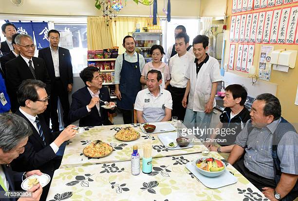 Japanese Prime Minister Shinzo Abe exchanges opinions with evacuees at a restaurant of a temporary housing during his visit on May 31, 2015 in...