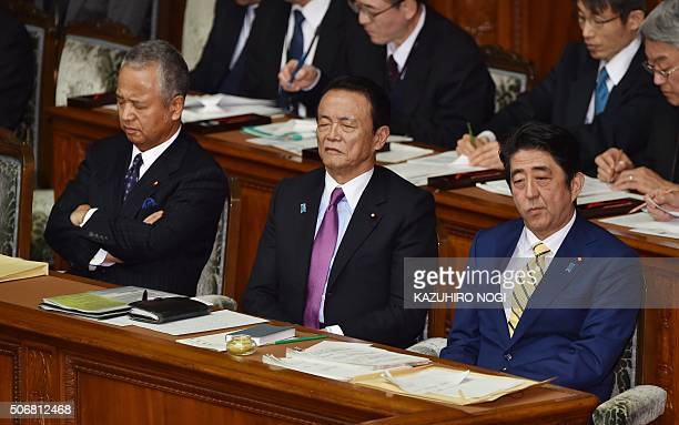 Japanese Prime Minister Shinzo Abe Finance Minister Taro Aso and Economy and Fiscal Policy Minister Akira Amari listen to questions by main...