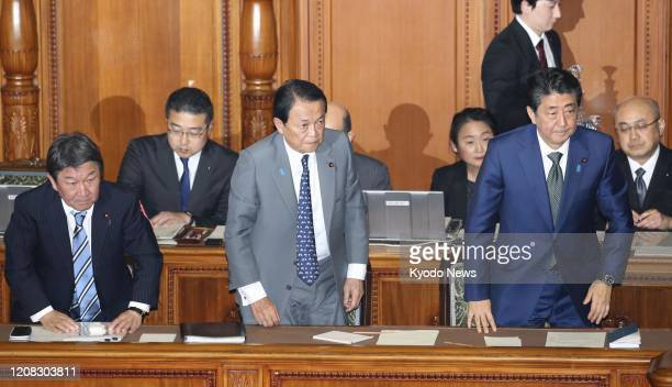 Japanese Prime Minister Shinzo Abe Finance Minister Taro Aso and Foreign Minister Toshimitsu Motegi bow after a record 10266 trillion yen budget for...