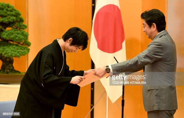 Japanese Prime Minister Shinzo Abe gives a certification of the People's Honor Award to Japanese figure skater Yuzuru Hanyu during its presentation...