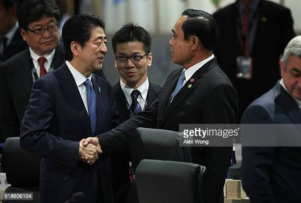 Japanese Prime Minister Shinzo Abe greets Prime Minister of Thailand Prayut Chan-o-cha during a plenary session of the 2016 Nuclear Security Summit...