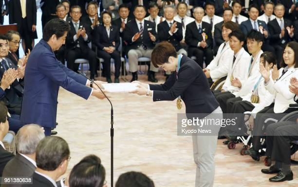 Japanese Prime Minister Shinzo Abe hands a commemorative gift to Pyeongchang Olympics speed skating gold medalist Nao Kodaira during a ceremony held...
