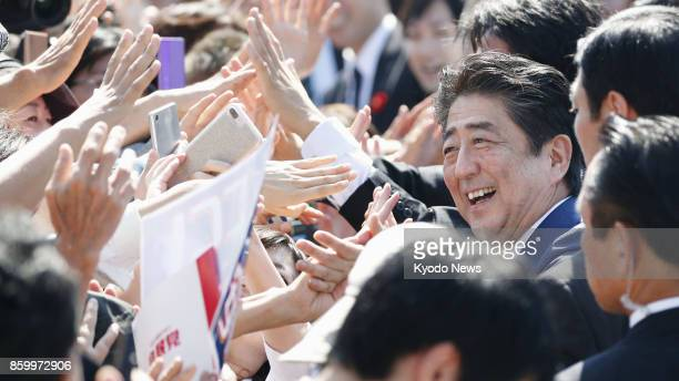Japanese Prime Minister Shinzo Abe head of the ruling Liberal Democratic Party greets the crowd after giving a stump speech in Shizuoka Prefecture's...