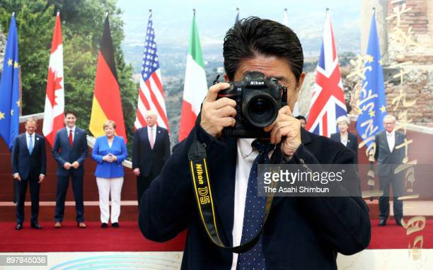 Japanese Prime Minister Shinzo Abe holds a camera during his visit to the 2017 Press Photo exhibition at Nihonbashi Mitsukoshi Department Store on...