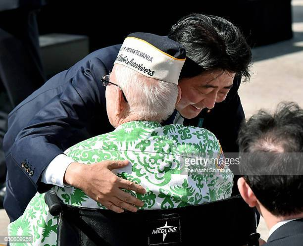 Japanese Prime Minister Shinzo Abe hugs a Pearl Harbor survivor at Joint Base Pearl Harbor Hickam's Kilo Pier on December 27 2016 in Honolulu Hawaii...
