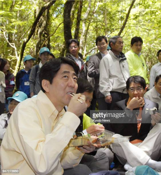 Japanese Prime Minister Shinzo Abe in this photo taken on May 26 eats his lunch during an ecology tour at Aokigahara forest in Fujikawaguchiko...