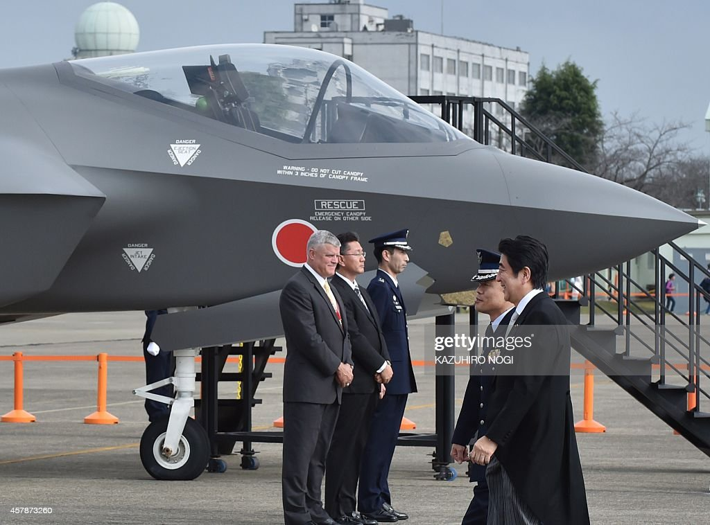 Japanese Prime Minister Shinzo Abe (R) inspects a mock-up F35A fighter (rear) as a static display during a review ceremony at the Japan Air Self-Defense Force's Hyakuri air base at Omitama in Ibaraki prefecture on October 26, 2014. 80 military aircrafts, 25 vehicles and 740 troops participated in the air review.