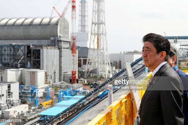 Japanese Prime Minister Shinzo Abe inspects the decommission work of the Tokyo Electric Power Co's Fukushima Daiichi Nuclear Power Plant on April 14...