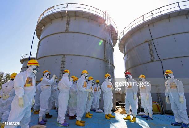 Japanese Prime Minister Shinzo Abe is briefed about tanks containing radioactive water by Fukushima Dai-ichi nuclear power plant chief Akira Ono in...