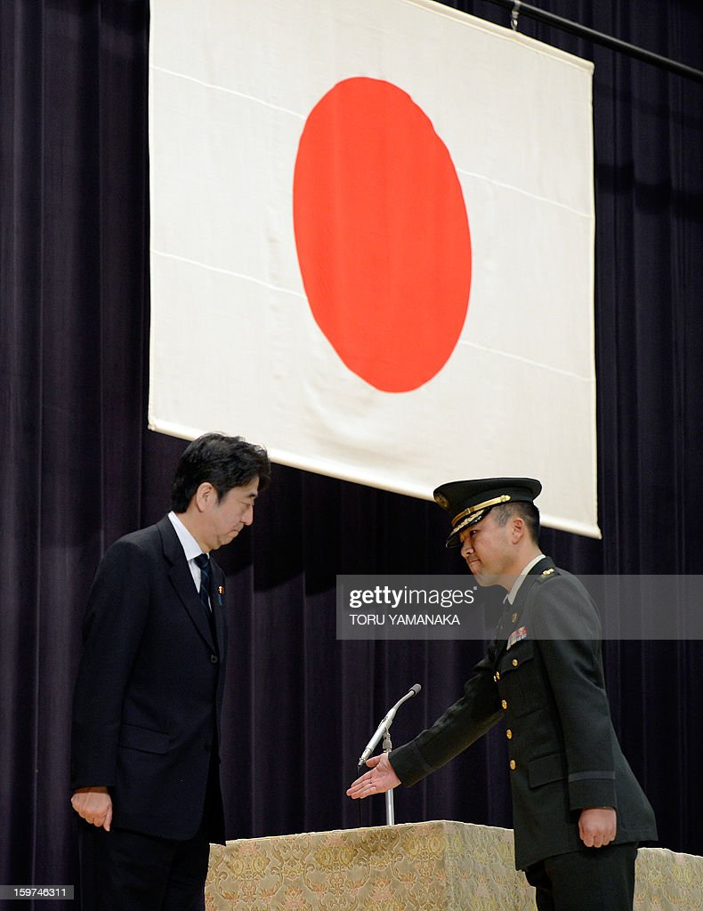 Japanese Prime Minister Shinzo Abe (C) is escorted by an officer as he attends flag return ceremony for the the United Nations assigned Japanese platoon at the Defence Ministry in Tokyo on January 20, 2013. All Japanese soldiers recently returned from United Nations peacekeeping operations assignment in the Golan Heights. AFP PHOTO/Toru YAMANAKA
