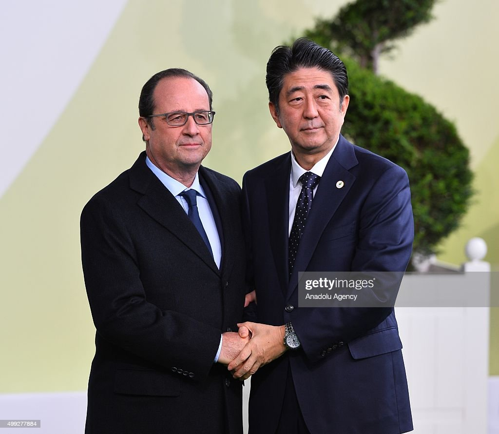 Japanese Prime Minister Shinzo Abe (R) is greeted by French President Francois Hollande (L) as he arrives for the COP21, United Nations Conference on Climate Change, in Le Bourget, north of Paris, France, on November 30, 2015.