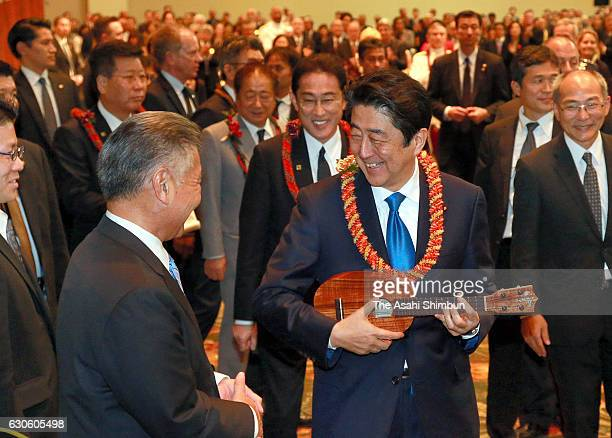 Japanese Prime Minister Shinzo Abe is presented an Ukulele from Hawaii Governor David Ige during a dinner with Japanese Americans on December 26 2016...