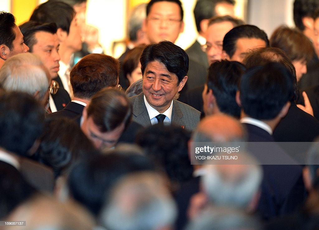 Japanese Prime Minister Shinzo Abe (C) is surrounded by Japan's business leaders after he made a speech at a New Year's party at a Tokyo hotel on January 7, 2013. Japan's major business lobbies said they support Prime Minister Abe for his efforts to revive the dwindling economy, urging him an early participation in a Pacific-wide free trade deal. AFP PHOTO / Yoshikazu TSUNO