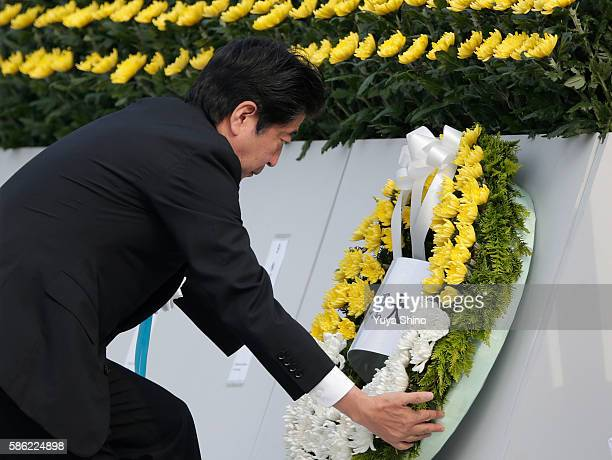 Japanese Prime Minister Shinzo Abe lays a wreath during the Hiroshima Peace Memorial Ceremony at Hiroshima Peace Memorial Park on August 6 2016 in...