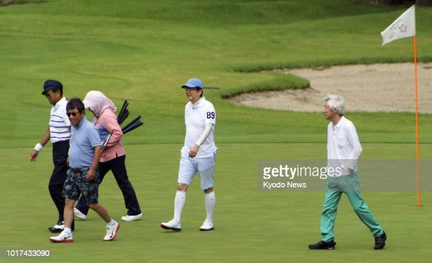 Japanese Prime Minister Shinzo Abe leaves a green on a golf course in Fujikawaguchiko Yamanashi Prefecture during his summer vacation on Aug 16 along...