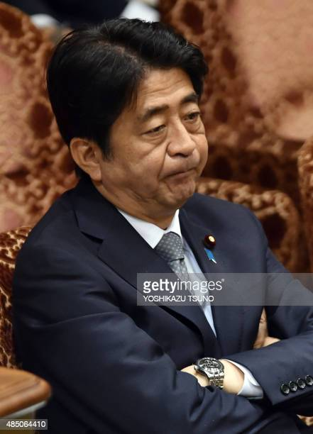 Japanese Prime Minister Shinzo Abe listens to a question by an opposition lawmaker at the Upper House's budget committee session at the National Diet...
