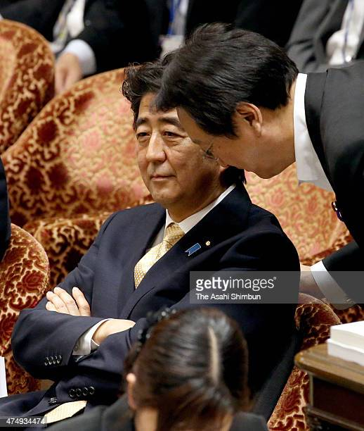 Japanese Prime Minister Shinzo Abe listens to Akinori Eto after taunting to lawmaker Kiyomi Tsujimoto during a special committee to deliberate the 11...