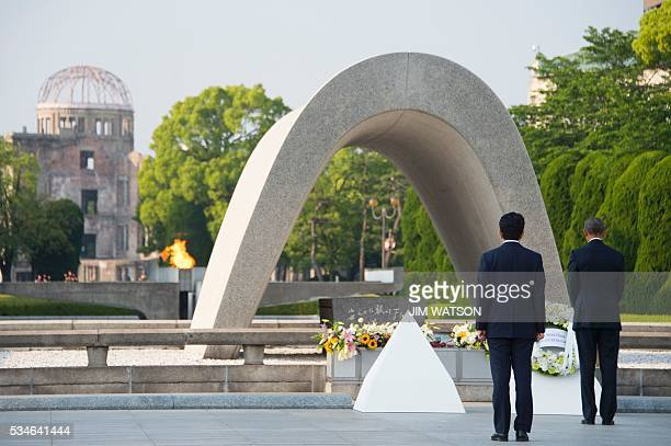 TOPSHOT Japanese Prime Minister Shinzo Abe looks on as US President Barack Obama lays a wreath during a visit to the Hiroshima Peace Memorial Park in...
