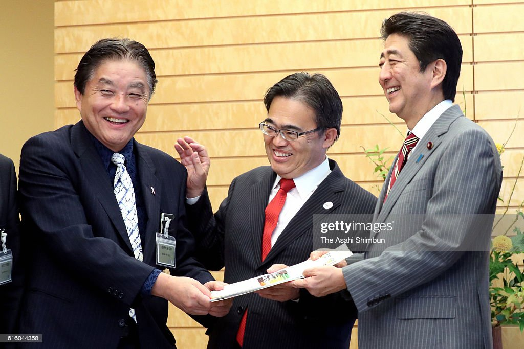 Japanese Prime Minister Shinzo Abe (R) meets Nagoya City mayor Takashi Kawamura (L) and Aichi Prefecture Governor Hideaki Omura (C) at his official residence on October 21, 2016 in Tokyo, Japan.