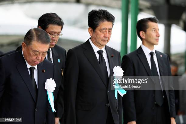 Japanese Prime Minister Shinzo Abe observes a minute of silence during the Peace Memorial Ceremony on the 74th anniversary of the atomic bombing of...